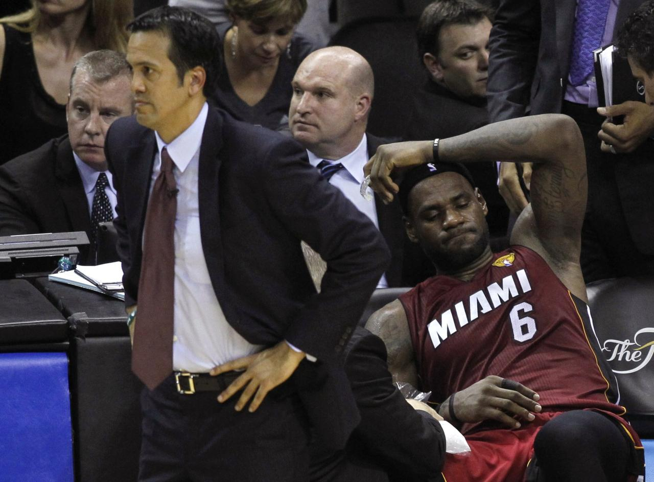 Miami Heat's LeBron James (R) sits on the bench after hurting his leg as coach Erik Spoelstra watches the game during the fourth quarter against the San Antonio Spurs in Game 1 of their NBA Finals basketball series in San Antonio, Texas June 5, 2014. REUTERS/Mike Stone (UNITED STATES - Tags: SPORT BASKETBALL TPX IMAGES OF THE DAY)