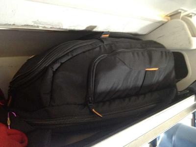 large carry-on bag in plane overhead bin compartment