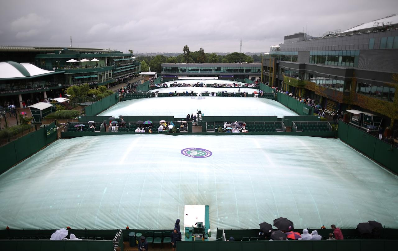 LONDON, ENGLAND - JUNE 28: Court covers keep the outside tennis courts dry during rain at the Wimbledon Lawn Tennis Championships on June 28, 2013 in London, England. Rain has delayed play on the outside courts today on day five of the tournament. (Photo by Peter Macdiarmid/Getty Images)