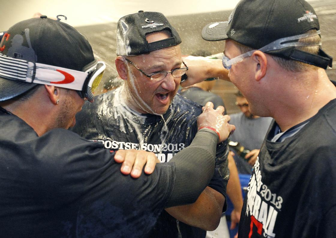 Cleveland Indians manager Terry Francona, center, is sprayed with champagne in the locker room after the Indians beat the Twins 5-1 in a baseball game in Minneapolis, Sunday, Sept. 29, 2013, to clinch a wild card spot in the playoffs. (AP Photo/Ann Heisenfel
