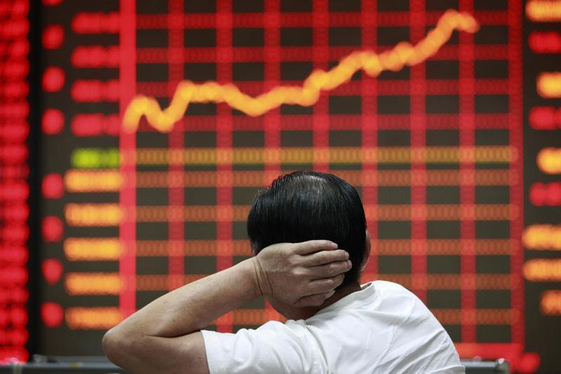 An investor looks at an electronic board showing stock information at a brokerage house in Huaibei