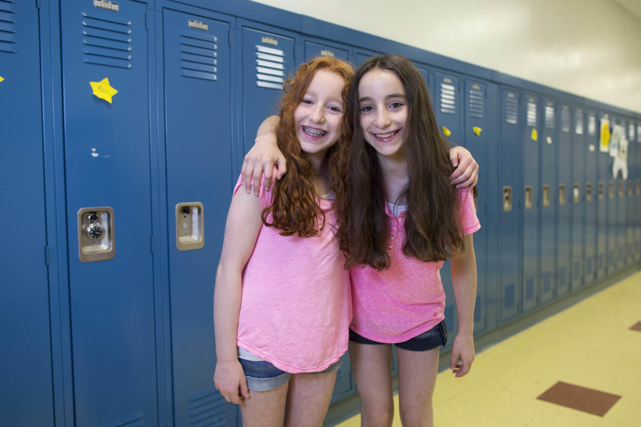 In this Thursday, June 6, 2013 photo, Amy Zun, left, and her twin sister, Rachel, one of the twenty-four sets of twins from Highcrest Middle School in Wilmette, Ill., pose for a portrait oat the school. The group is attempting to break a Guinness World record for the amount of twins in one grade which is currently 16 sets. (AP Photo/Scott Eisen)