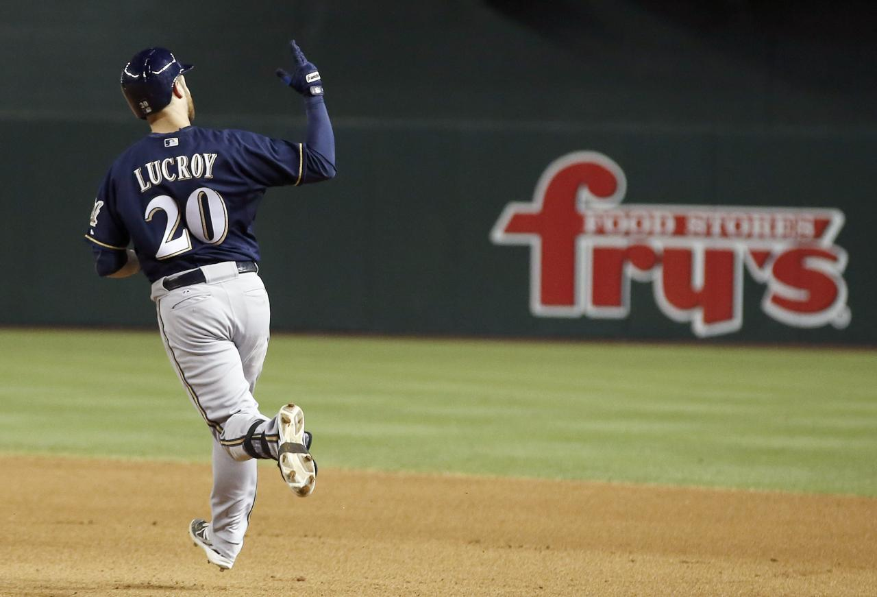 Milwaukee Brewers' Jonathan Lucroy raises his arm in celebration as he rounds the bases after hitting a grand slam against the Arizona Diamondbacks during the seventh inning of a baseball game on Tuesday, June 17, 2014, in Phoenix. (AP Photo/Ross D. Franklin)