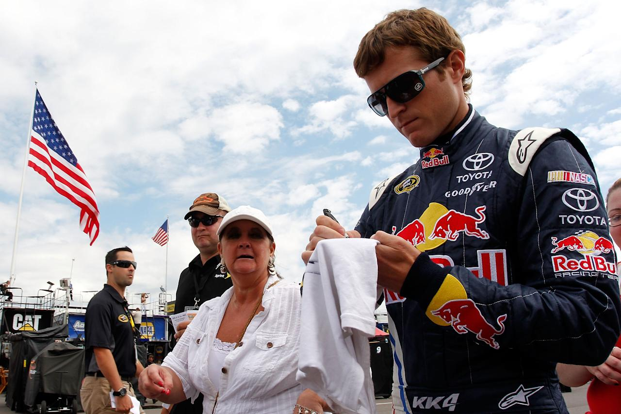 LONG POND, PA - AUGUST 05:  Kasey Kahne, driver of the #4 Red Bull Toyota, signs autographs during practice for the NASCAR Sprint Cup Series Good Sam RV Insurance 500 at Pocono Raceway on August 5, 2011 in Long Pond, Pennsylvania.  (Photo by Geoff Burke/Getty Images for NASCAR)
