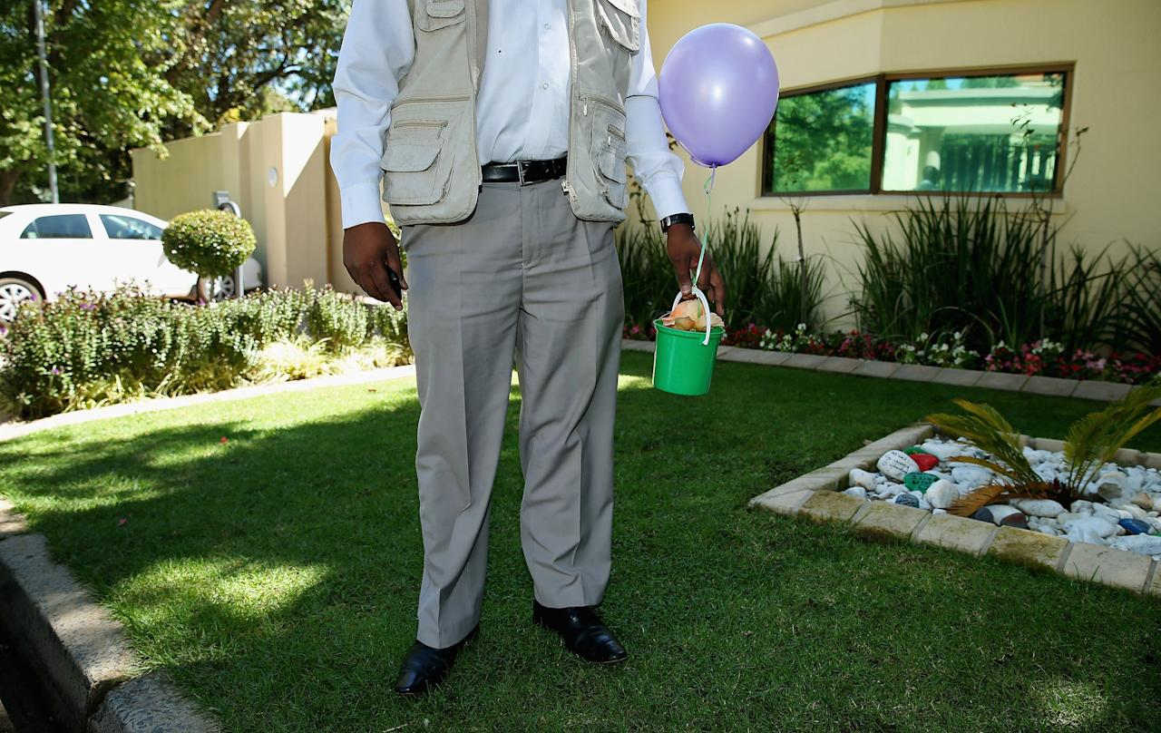 JOHANNESBURG, SOUTH AFRICA - APRIL 06:  A security guard holds a small get-well gift and balloon from two-year-old Kristen Lewis outside the home of former South African President Nelson Mandela during Kristen's second birthday party in the Houghton neighborhood of Johannesburg on April 6, 2013 in South Africa. Kristen and her birthday party guests deliverd the gift and placed painted rocks in planters outside the home of the former president. Mandela, 94, was dischared after spending more than a week at a hospital in Pretoria being treated for pneumonia.  (Photo by Chip Somodevilla/Getty Images)