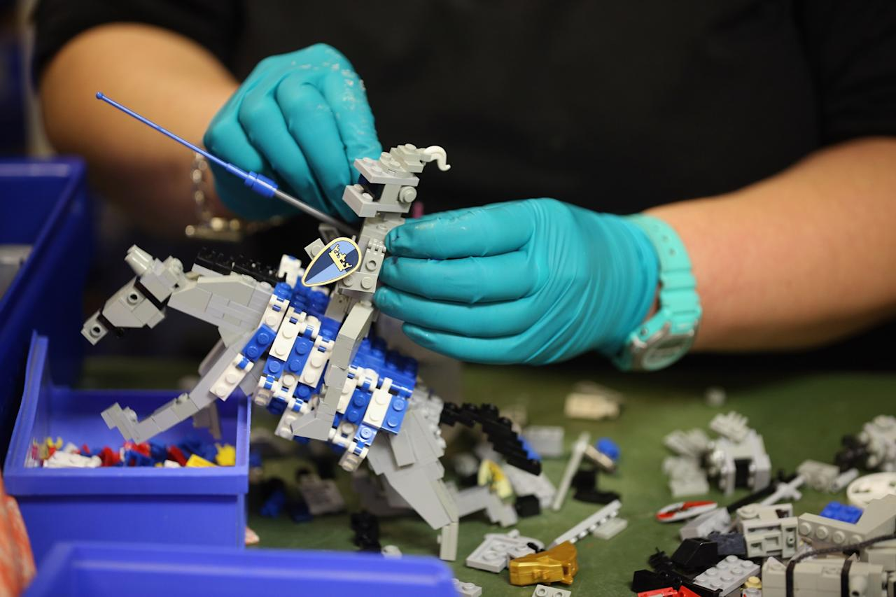 WINDSOR, ENGLAND - JULY 03: Paula Laughton, a Model Maker, creates LEGO models for a jousting scene in the Model Making Studio at the LEGOLAND Windsor Resort on July 3, 2013 in Windsor, England. LEGOLAND Windsor Resort, which has been open since 1996, has 55 interactive rides and attractions and thousands of LEGO models made from around 80 million individual bricks. LEGOLAND Windsor employs 4 Model Makers who design, build and maintain all of the LEGO models on site. (Photo by Oli Scarff/Getty Images)