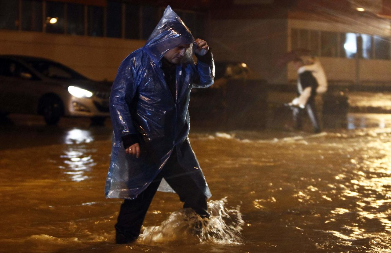 A man walks along a flooded street in Sochi, September 24, 2013. Regional authorities have declared a state of emergency in the area around Sochi because of flooding and mudslides less than five months before the Russian city hosts the Winter Olympics. Picture taken September 24, 2013. REUTERS/Maxim Shemetov (RUSSIA - Tags: ENVIRONMENT SPORT OLYMPICS)