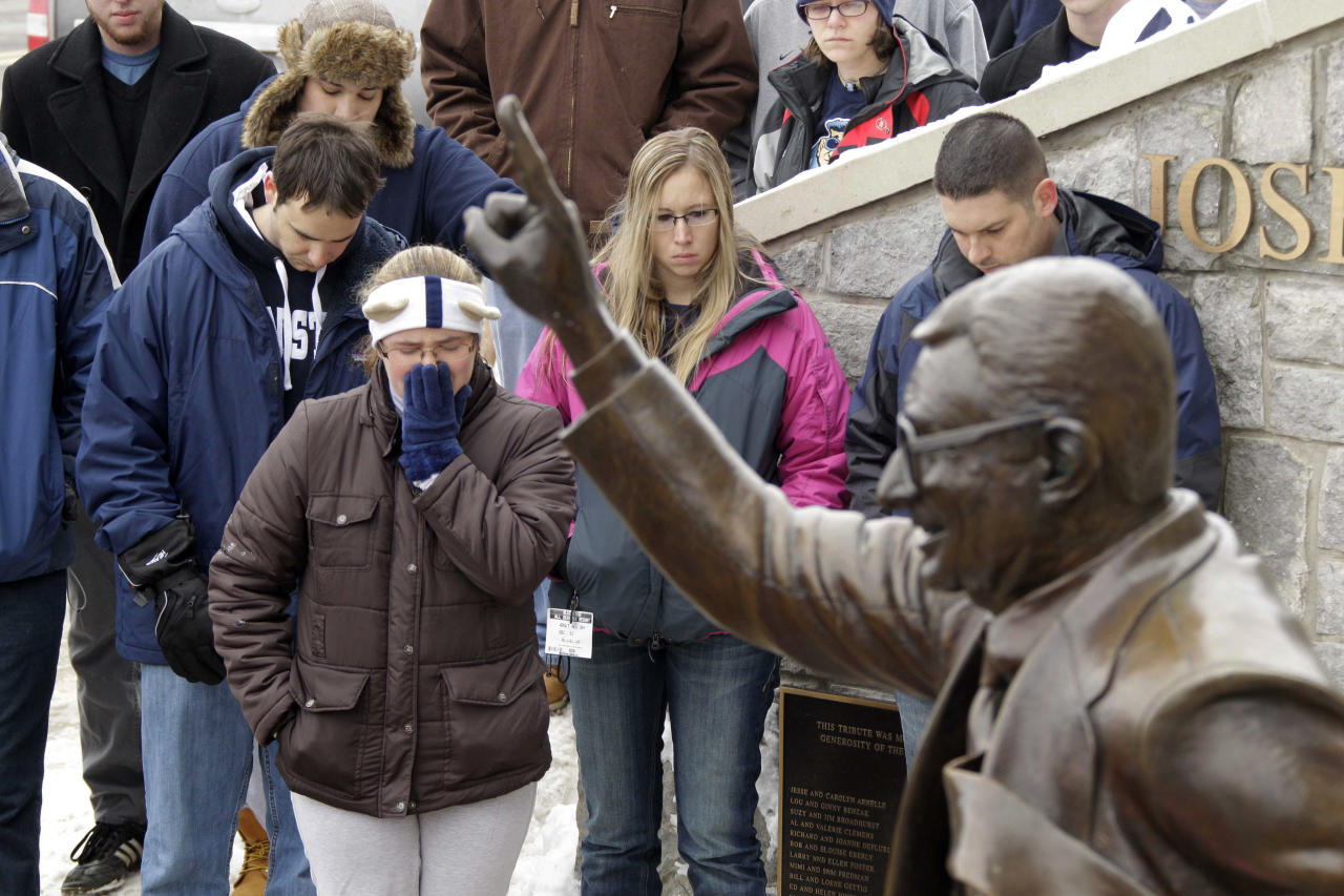 People gather around a statue of Joe Paterno outside Beaver Stadium on the Penn State University campus after learning of his death Sunday, Jan. 22, 2012 in State College,Pa. (AP Photo/Gene J. Puskar)