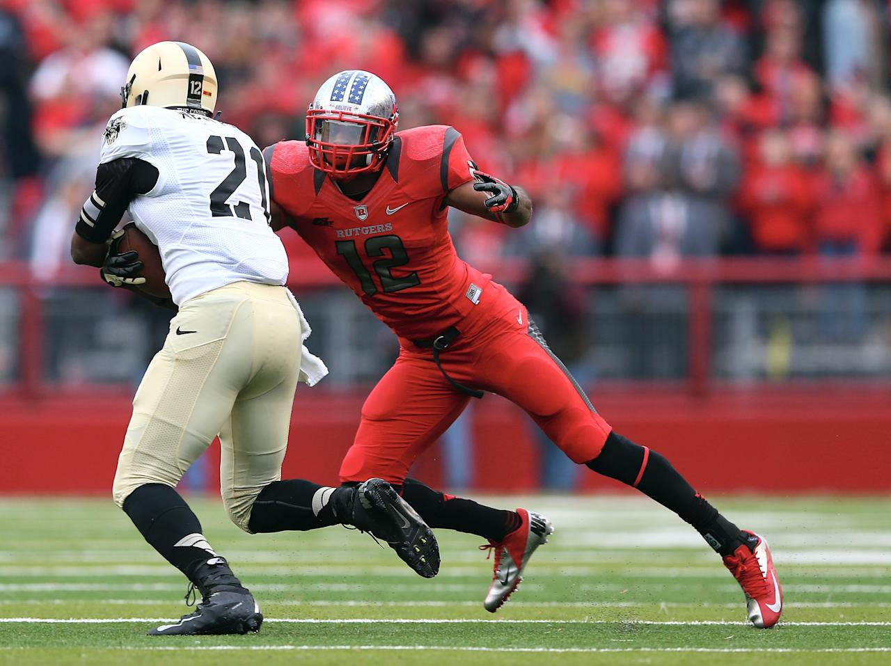 PISCATAWAY, NJ - NOVEMBER 10:  Marcus Cooper #12 of the Rutgers Scarlet Knights tackles Chevaughn Lawrence #21 of the Army Black Knights   on November 10, 2012 at High Point Solutions Stadium in Piscataway, New Jersey.The Rutgers Scarlet Knights defeated the Army Black Knights 28-7.  (Photo by Elsa/Getty Images)
