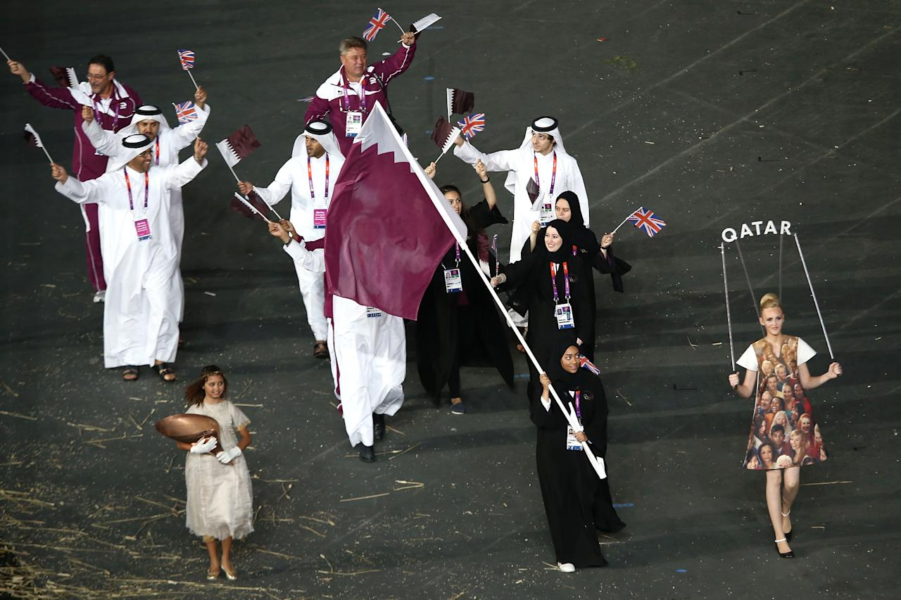 LONDON, ENGLAND - JULY 27: Bahya Mansour Al Hamad of the Qatar Olympic shooting team carries her country's flag during the Opening Ceremony of the London 2012 Olympic Games at the Olympic Stadium on July 27, 2012 in London, England.  (Photo by Quinn Rooney/Getty Images)