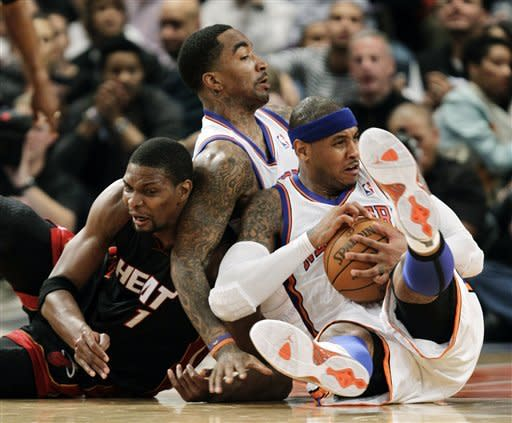 Miami Heat forward Chris Bosh (1), New York Knicks guard J.R. Smith, center, and Knicks forward Carmelo Anthony scramble for a loose ball in the first half of Game 3 of an NBA basketball first-round playoff series at Madison Square Garden in New York, Thursday, May 3, 2012. (AP Photo/Kathy Willens)