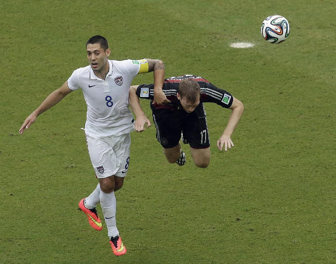 United States' Clint Dempsey (8) and Germany's Per Mertesacker battle for the ball during the group G World Cup soccer match between the USA and Germany at the Arena Pernambuco in Recife, Brazil, Thursday, June 26, 2014. (AP Photo/Hassan Ammar)