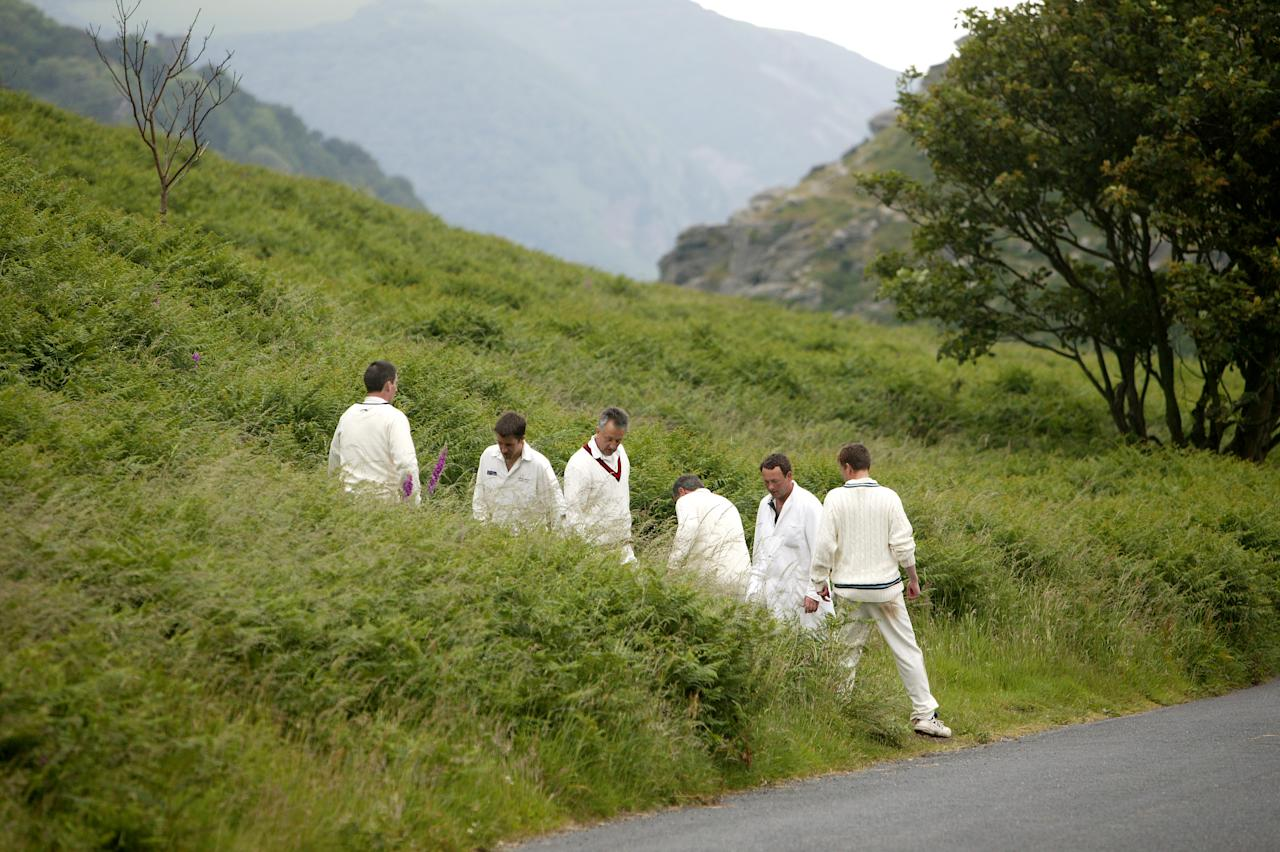 "LYNTON AND LYNMOUTH, ENGLAND - JUNE 26:  Cricketers from Lynton and Lynmouth Cricket Club look for a lost ball in the ""Valley of The Rocks"" on June 26, 2005 in Lynton and Lynmouth, England.  (Photo by Laurence Griffiths/Getty Images)"