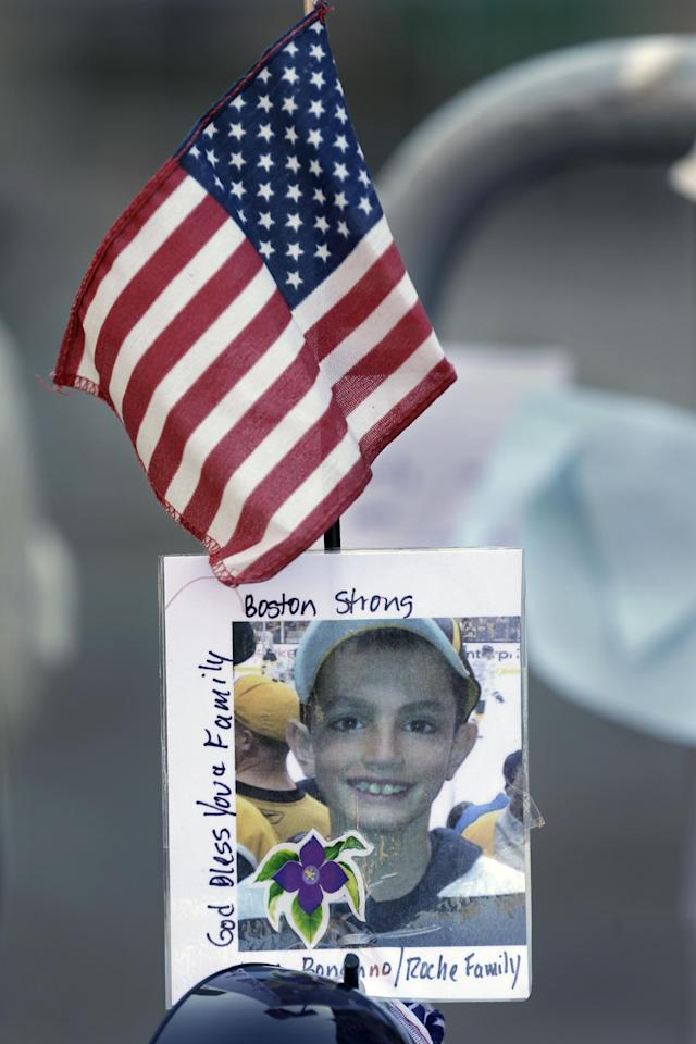 A photograph of bombing victim Martin Richard, 8, is attached to a barricade in Boston, Monday, April 22, 2013, at a makeshift memorial on the street not far from where two bombs exploded near the finish line of the Boston Marathon, Monday, April 15, 2013. Richard was among three people killed in the bombings at the finish line of the race last Monday. (AP Photo/Steven Senne)