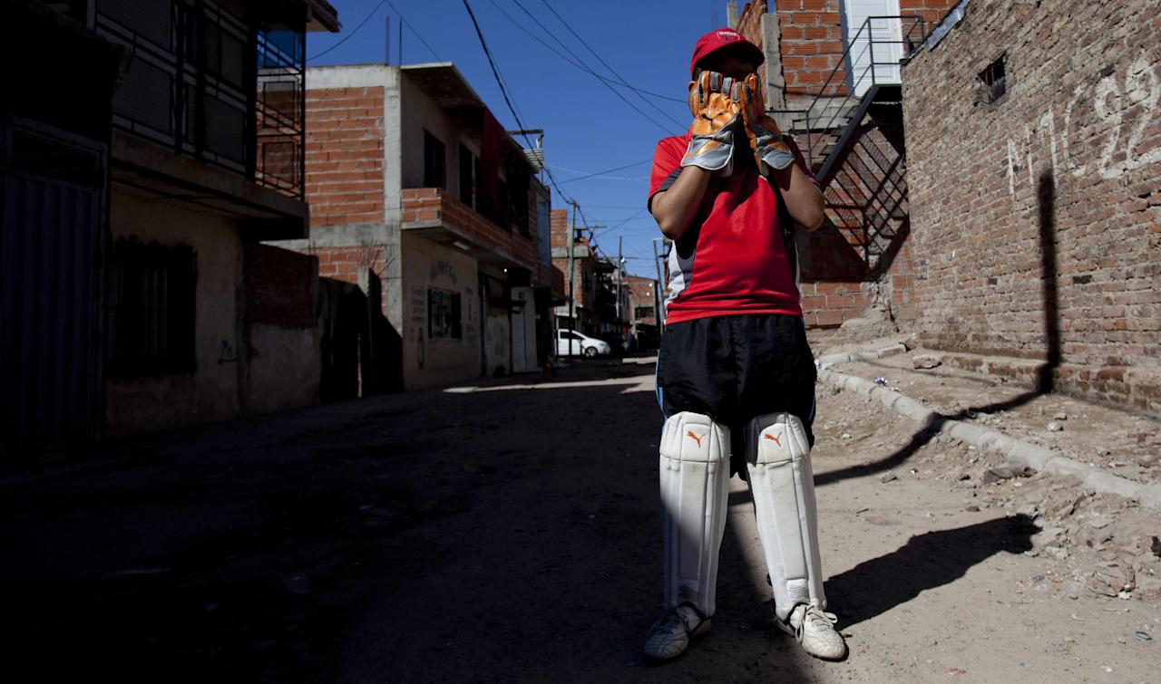 Caacupe cricket team member Alejandro Mercado covers his face with his gloved hands during a training session at the Villa 21-24 slum in Buenos Aires, Argentina, Saturday, March 22, 2014. The International Cricket Council has recognized the team, formed from the children of the Villa 21-24 shantytown, honoring them as a global example for expanding the sport, which in certain countries, like India, is widely played, but in many parts of the world restricted to elite sectors of society. Introducing cricket in the slum began in 2009 as an idea to transform the game into a social integration mechanism, before that it rarely breached the gates of the country's upscale private schools. (AP Photo/Natacha Pisarenko)