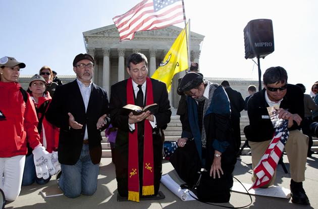 From left, Janis Haddon of Atlanta, Rev. Patrick J. Mahoney, director of the Christian Defense Coaltion, Rev. Rob Schenck, president of the National Clergy Council, Linda Door of Laguna Beach, Ca., and Ken Campbell of the Tea Party Patriots, pray in front of the Supreme Court.