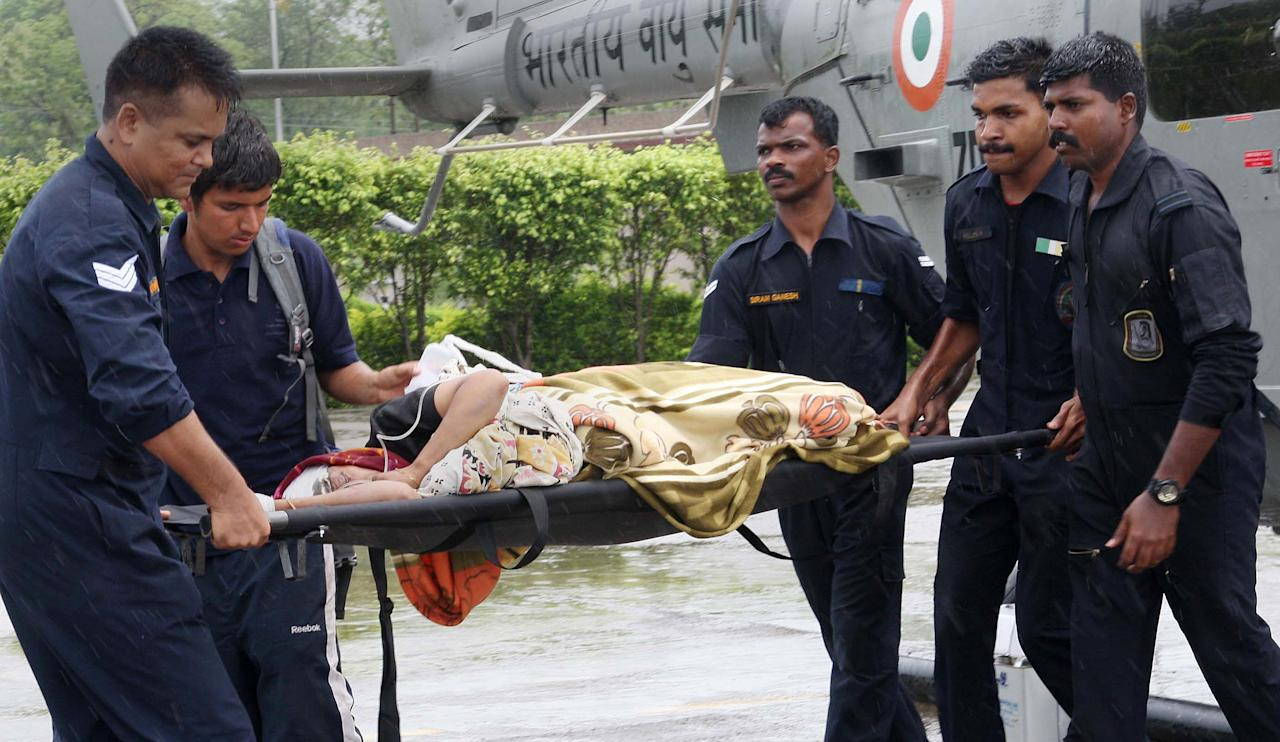In this handout photograph received from the Ministry of Defence (MOD) on June 27, 2013 personel transport a rescued person on a stretcher from a helicopter at Jolly Grant airport in Dehradun in the northern Uttarakhand state.  Rescue workers stepped up the search for bodies June 27 in India's flood ravaged north, as mass cremations of victims already discovered got underway amid fears of outbreaks of disease , officials and reports said.   AFP PHOTO / MOD / NARESH KUMAR