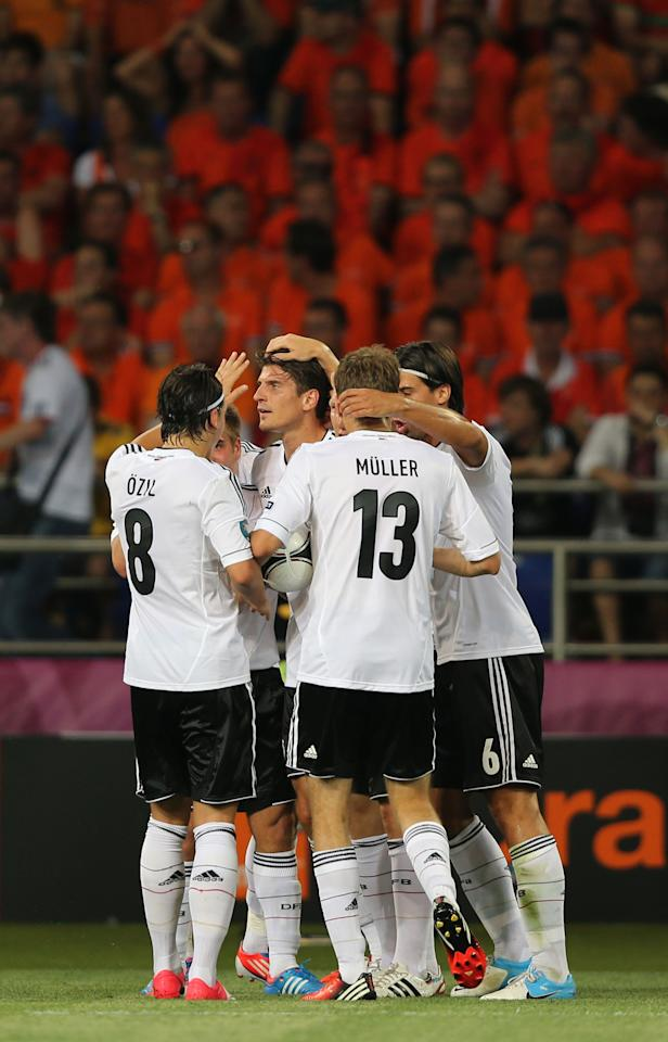 KHARKOV, UKRAINE - JUNE 13:  Mario Gomez of Germany celebrates scoring the opening goal with team mates during the UEFA EURO 2012 group B match between Netherlands and Germany at Metalist Stadium on June 13, 2012 in Kharkov, Ukraine.  (Photo by Ian Walton/Getty Images)