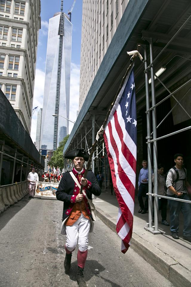 """With the new WorldTrade Center tower as a backdrop, a flag bearer in American revolutionary costume leads the """"Old Barracks Fife and Drum Corps,"""" from Trenton, N.J., in a Flag Day procession along Fulton Street on Friday, June 14, 2013 in New York. (AP Photo/Bebeto Matthews)"""