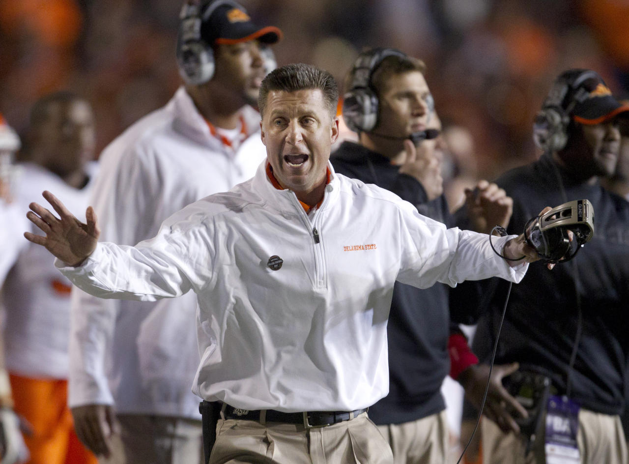 Oklahoma State coach Mike Gundy tries to get the attention of an official during the first half of an NCAA college football game against Kansas State in Manhattan, Kan., Saturday, Nov. 3, 2012. (AP Photo/Orlin Wagner)