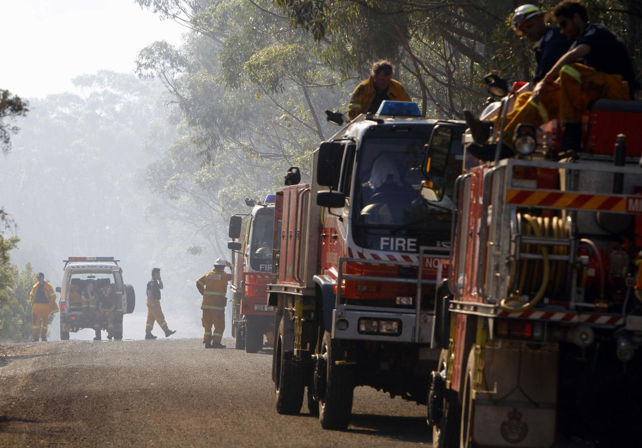 Rural Fire Service (RFS) firefighters take a break after trying to extinguish a fire approaching homes near the Blue Mountains suburb of Faulconbridge, located around 80 km (50 miles) west of Sydney October 24, 2013. A plane dousing wildfires in bushland south of Australia's biggest city, Sydney, crashed into a national park on Thursday, killing the pilot and sparking a new fire to add to 55 still burning across the state of New South Wales. The accident happened as more dry, windy conditions caused a flare-up in huge fires burning for a week in mountains to the west of Sydney, closing roads and entering a valley running down towards the metropolitan area. REUTERS/Rick Stevens (AUSTRALIA - Tags: DISASTER ENVIRONMENT)