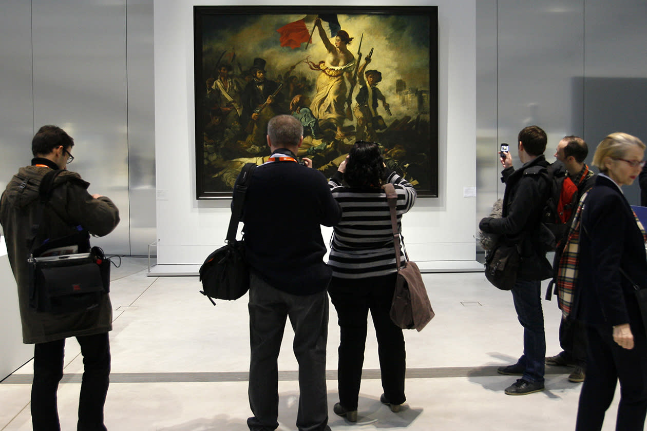 "Journalists take photos in front of "" La Liberte Guidant le Peuple"" a painting by Eugene Delacroix."