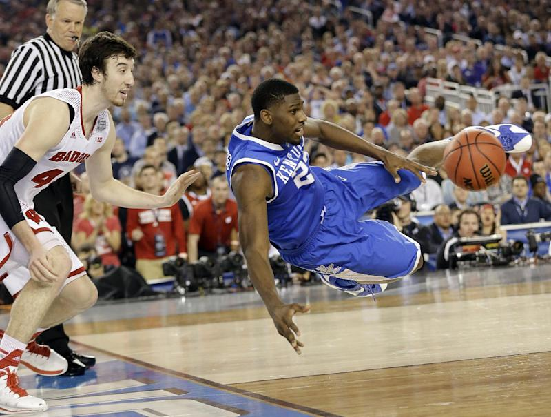 Kentucky forward Alex Poythress (22) saves the ball from going out as Wisconsin forward Frank Kaminsky (44) defends during the second half of the NCAA Final Four tournament college basketball semifinal game Saturday, April 5, 2014, in Arlington, Texas