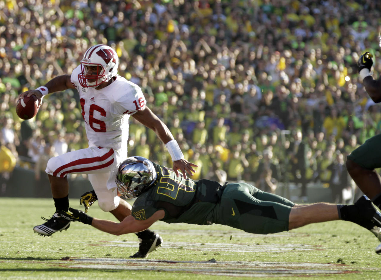 Wisconsin quarterback Russell Wilson breaks a tackle from Oregon's Kiko Alonso during the first half of the Rose Bowl NCAA college football game, Monday, Jan. 2, 2012, in Pasadena, Calif. (AP Photo/Matt Sayles)