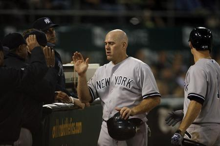 Yankees' Youkilis high fives teammates after scoring from a single during the seventh inning against the Athletics in his MLB American League game in Oakland