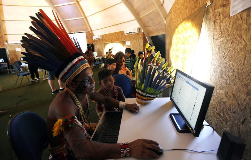 Brazilian indigenous people use computers inside a tent during the XII Games of the Indigenous People in Cuiaba