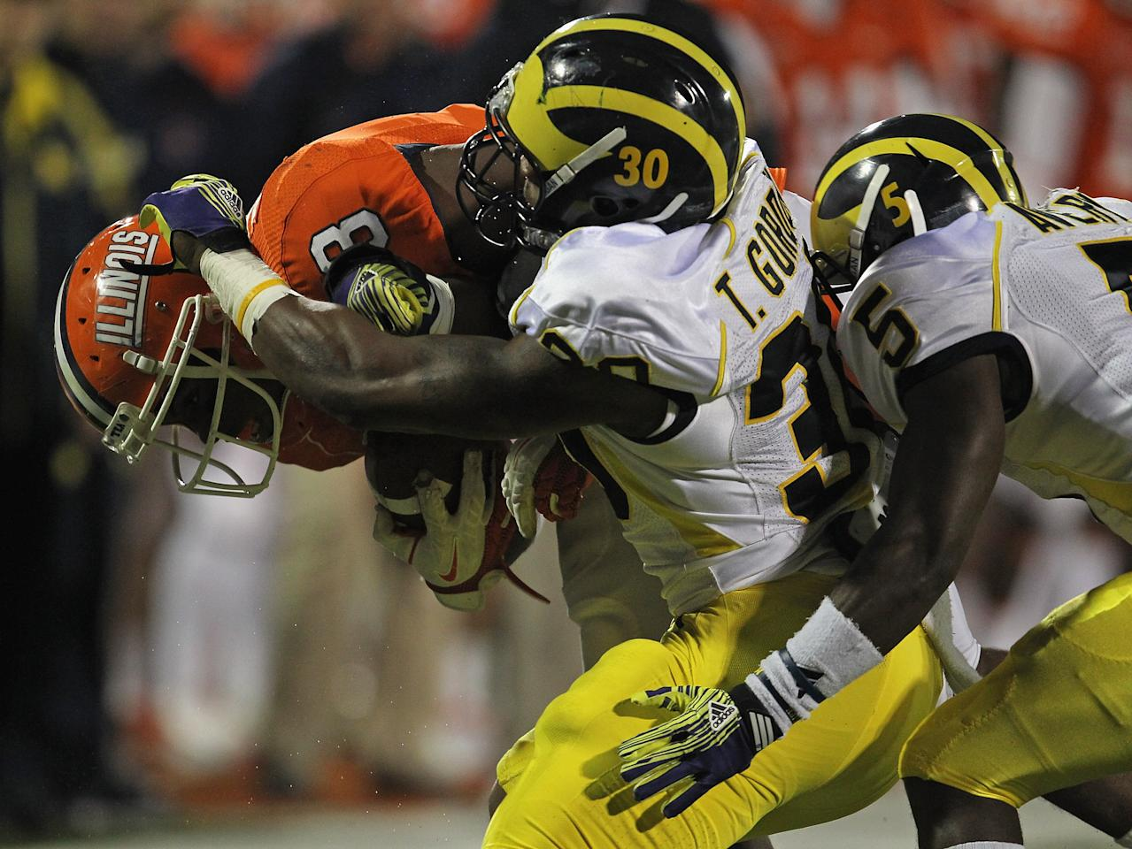 CHAMPAIGN, IL - NOVEMBER 12: Jon Davis #3 of the Illinois Fighting Illini is hit by Thomas Gordon #30 and Courtney Avery #5 of the Michigan Wolverines at Memorial Stadium on November 12, 2011 in Champaign, Illinois. Michigan defeated Illinois 31-14. (Photo by Jonathan Daniel/Getty Images)