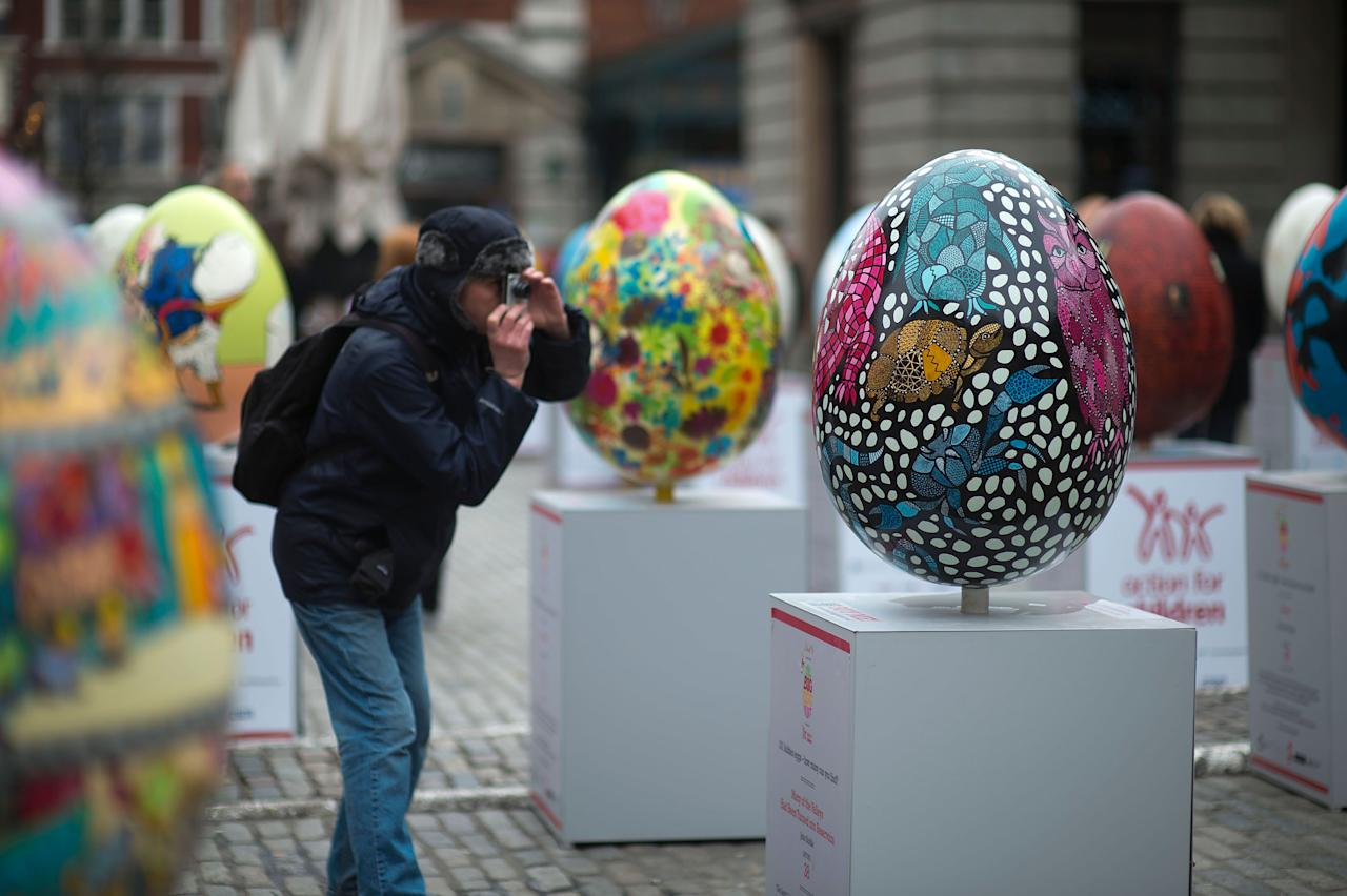LONDON, ENGLAND - MARCH 22: A visitor photographs a giant fibreglass easter egg entitled 'Many Of The Valleys Had Been' by John Biddle which is on display in Covent Garden before the Big Egg Hunt on March 22, 2013 in London, England. Each egg is two and a half feet tall and designed by a leading artist. (Photo by Bethany Clarke/Getty Images)
