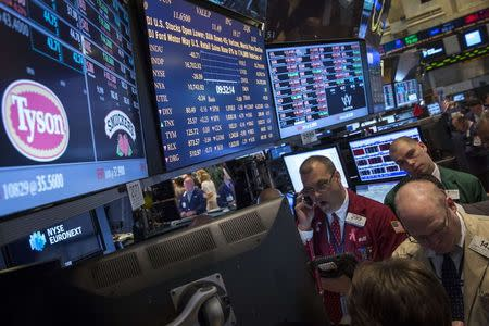 Traders gather at the post that trades Tyson Foods on the floor of the New York Stock Exchange