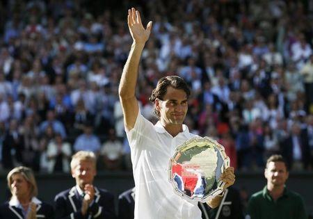 Roger Federer of Switzerland waves while holding the runner-up's trophy after being defeated by Novak Djokovic of Serbia in their men's singles finals tennis match on Centre Court at the Wimbledon Tennis Championships in London