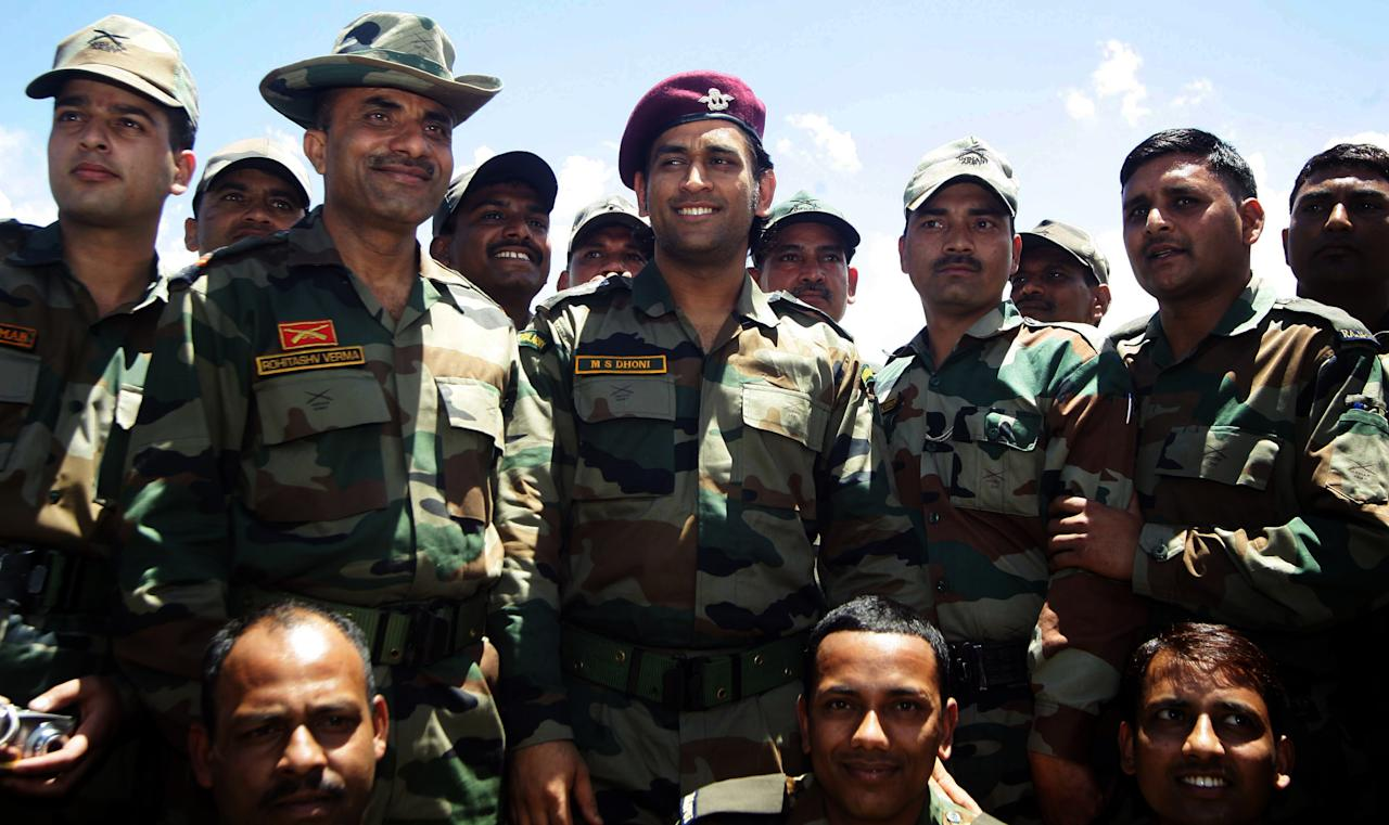 Indian cricket team captain and honorary Lieutenant Colonel in the Indian Territorial Army, Mahendra Singh Dhoni (C) poses with army officers during his two day visit to the India-Pakistan Line of Control at Bhimbher Gali forward post about 200 km from Jammu, the winter capital of Kashmir on June 2, 2012. Dhoni was commissioned in the Territorial Army and became an honorary Lieutenant Colonel in 2011, and this is his first official visit to forward posts of Rajouri and Poonch districts of Jammu region. AFP PHOTO/ STR (Photo credit should read STRDEL/AFP/GettyImages)