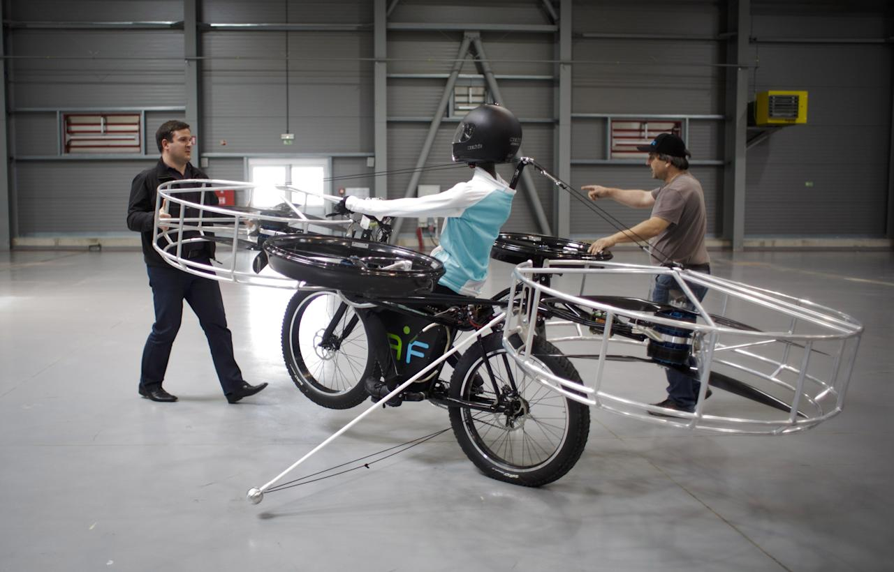 Technicians prepare a 'Flying bike' bicycle ahead of its first public flight on June 12, 2013 in Prague, Czech Republic. The bike has been manufactured by 3 different companies from the Czech Republic (Duratec, Technodat, Evektor) and has been supported by French Company Dassault System. The F-Bike has four main motors (10kW) and two stabilization motors (3,5 kW). It has an estimated constant flight time of 3-5 minutes.  (Photo by Matej Divizna/Getty Images)