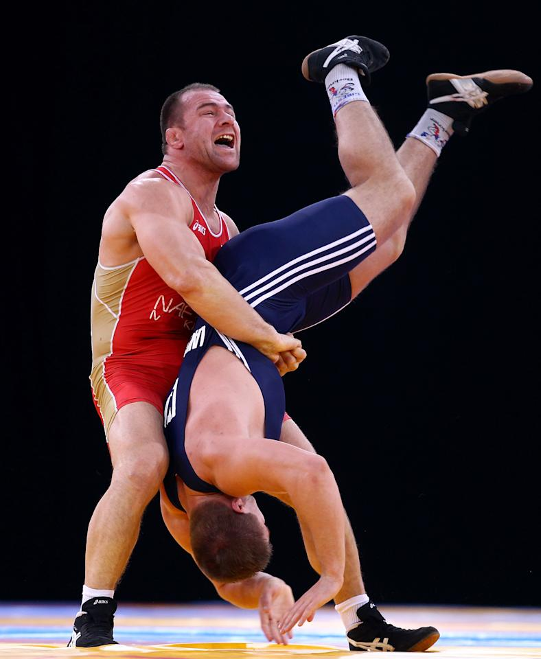 LONDON, ENGLAND - DECEMBER 10:  Aslanbek Khushtov of Russia lifts Vilius Laurinatis of Lithuania upside down in a 96k Men's Greco-Roman bout during the Wrestling LOCOG Test Event for London 2012 at ExCel on December 10, 2011 in London, England.  (Photo by Julian Finney/Getty Images)