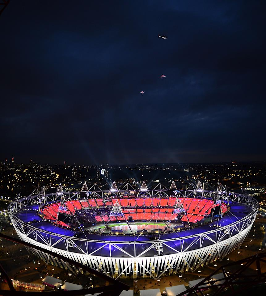 LONDON, ENGLAND - JULY 27:  Sky divers dressed as the Queen and James Bond parachute from a helicopter over the Olympic Stadium during the Opening Ceremony for the 2012 Olympic Games on July 27, 2012 at Olympic Park in London, England.  (Photo by Jamie Squire/Getty Images)