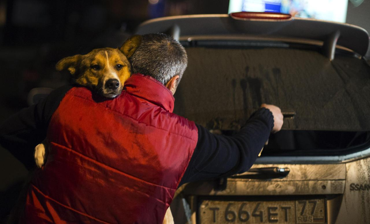 Animal activist Igor Airapetian carries a stray dog to his car brought out of Sochi by fellow activist at a rendezvous point 120 kilometers away from the Olympic area in the early morning hours of Tuesday, Feb. 11, 2014, in Tuapse, Russia. Airapetian is one of a dozen people in the emerging movement of animal activists in Sochi alarmed by reports that the city has contracted the killing of thousands of stray dogs before and during the Olympic Games. Stray dogs are a common sight on the streets of Russian cities, but with massive construction in the area the street dog population in Sochi and the Olympic park has soared. Useful as noisy, guard dogs, workers feed them to keep them nearby and protect buildings. They soon lose their value and become strays. Tonight, a few dogs will be taken on their way to a new life in Moscow. (AP Photo/David Goldman)