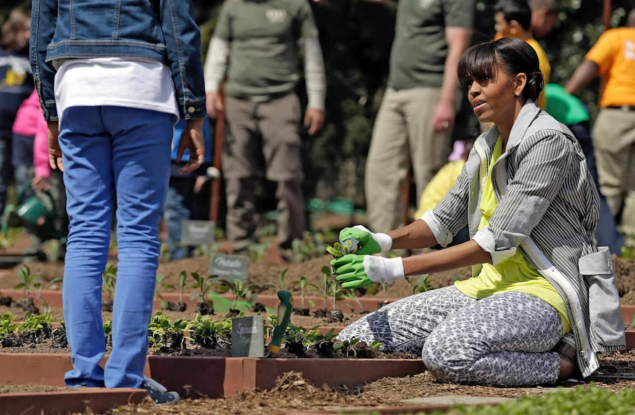 """WASHINGTON, DC - APRIL 04:  U.S. first lady Michelle Obama plants the White House Kitchen Garden on the South Lawn of the White House April 4, 2013 in Washington, DC. For the fifth time, the first lady invited students from """"schools that have made exceptional improvements to school lunches"""" from Florida, Massachusetts, Tennessee and Vermont to help her plant the garden.  (Photo by Win McNamee/Getty Images)"""