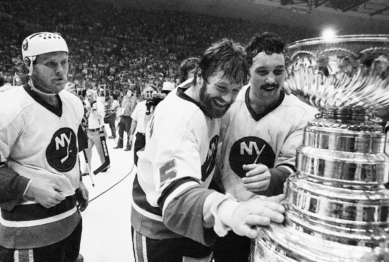 FILE - In this May 24, 1980, file photo, New York Islanders captain Denis Potvin (5) reaches out to touch the Stanley Cup trophy as teammate Brian Trottier, right, looks on after the Islanders won the NHL's Stanley Cup championship by defeating the Philadelphia Flyers 5-4 in overtime in Game 6 at Nassau Coliseum in Uniondale, N.Y. A person familiar with the situation says the Islanders have struck a deal to move to Brooklyn's Barclays Center as early as 2015. The person was not authorized to discuss the situation prior to an afternoon announcement, Wednesday, Oct. 24, 2012, and spoke to The Associated Press on condition of anonymity. (AP Photo/Richard Drew, File)
