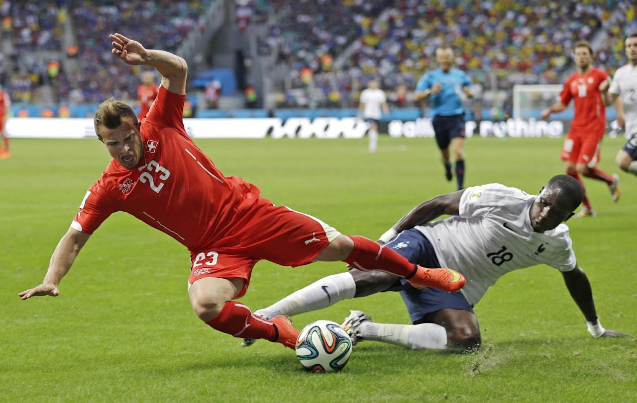 Switzerland's Xherdan Shaqiri is tripped by France's Moussa Sissoko during the group E World Cup soccer match between Switzerland and France at the Arena Fonte Nova in Salvador, Brazil, Friday, June 20, 2014. (AP Photo/Natacha Pisarenko)