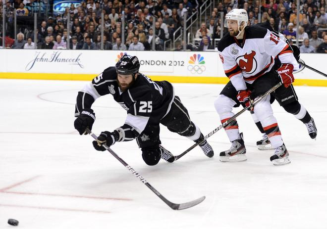 LOS ANGELES, CA - JUNE 04:  Dustin Penner #25 of the Los Angeles Kings dives to play the puck as Travis Zajac #19 of the New Jersey Devils looks on during Game Three of the 2012 Stanley Cup Final at Staples Center on June 4, 2012 in Los Angeles, California.  (Photo by Harry How/Getty Images)