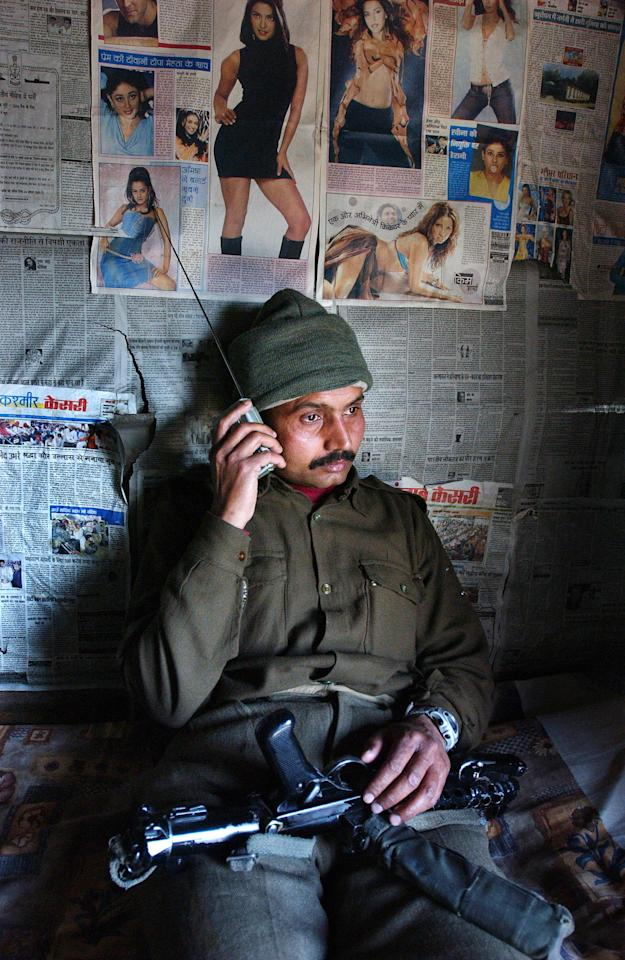 SRINAGAR, KASHMIR, INDIA - MARCH 13: An Indian Border Security Force soldier listens to the Indian cricket team play Pakistan on his radio in the first one-day international cricket match held in Karachi, Pakistan, March 13, 2004 at their camp in Srinagar, India. This is the first cricket tour held in Pakistan between the two nations in 14 years.  (Photo by Ami Vitale/Getty Images)