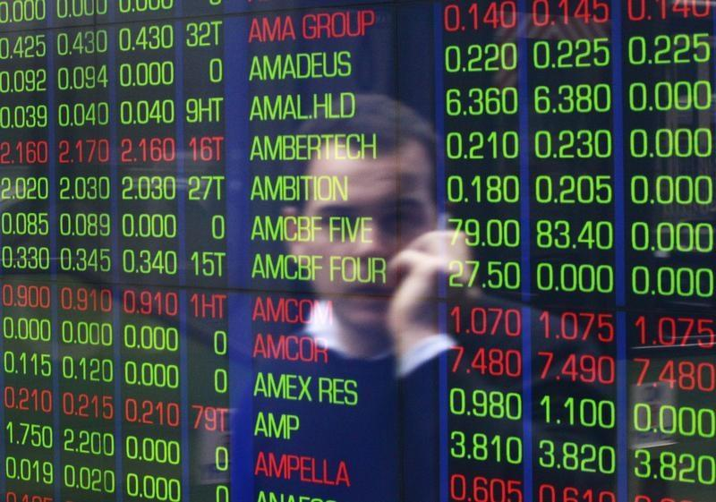 An office worker talks on his phone as he looks the stock board at the Australian Securities Exchange building in Sydney