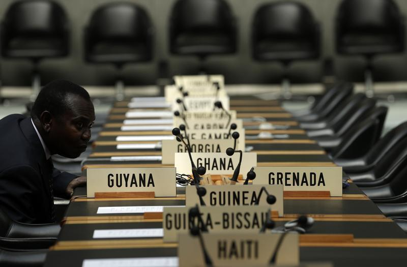 A delegate waits for the opening of a session of the Trade Negotiation Committee at the WTO in Geneva