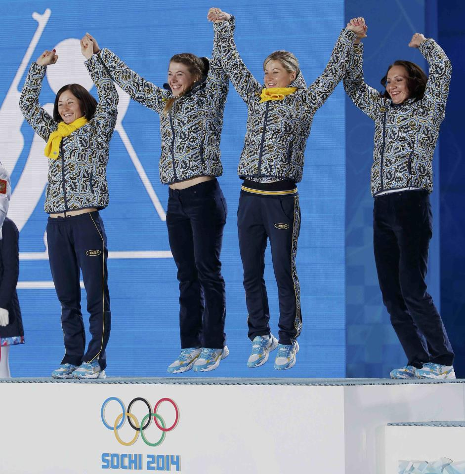Gold medallists Ukraine's Juliya Dzhyma (2nd L), Vita Semerenko, Valj Semerenko and Olena Pidhrushna (R) jump on the podium during the victory ceremony for the women's biathlon 4 x 6km event at the 2014 Sochi Winter Olympics February 22, 2014. REUTERS/Jim Young (RUSSIA - Tags: OLYMPICS SPORT BIATHLON TPX IMAGES OF THE DAY)