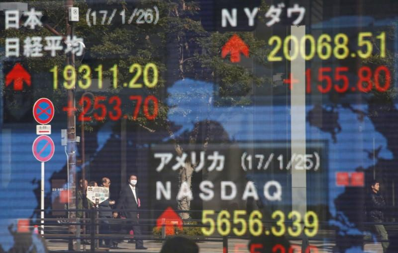 Pedestrians are reflected on an electronic board showing Japan's Nikkei average the Dow Jones average and the stock averages of other countries outside a brokerage in Tokyo