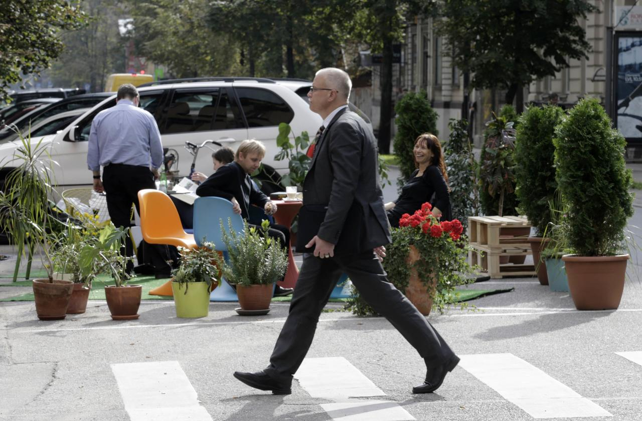 A man crosses a street past people participating in a PARK(ing) Day event in Riga, September 20, 2013. The event aims to transform metered parking spaces into temporary public places to call attention to the need for more urban open spaces and discuss the creation and allocation of public spaces, according to organizers. REUTERS/Ints Kalnins (LATVIA - Tags: SOCIETY)