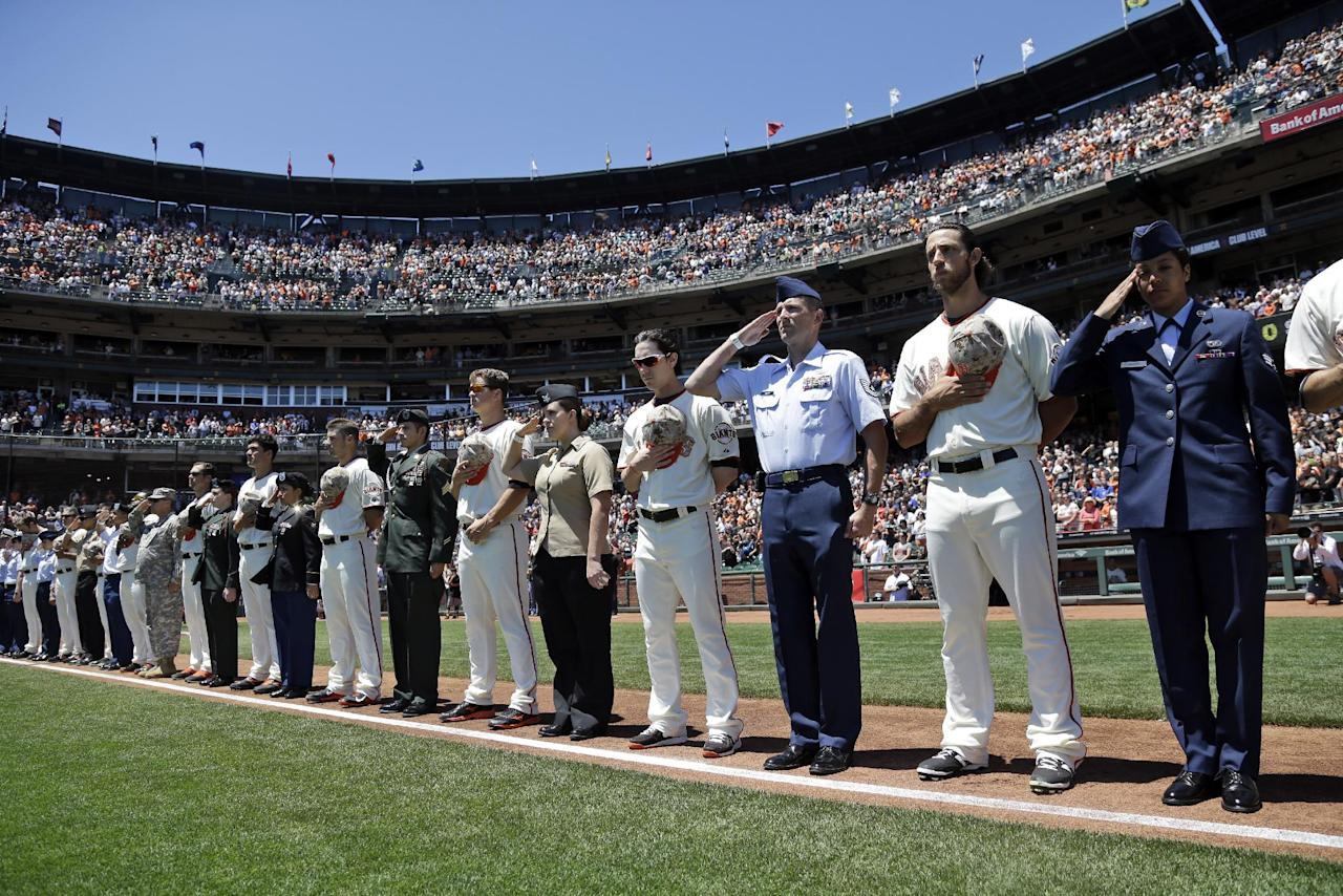 The San Francisco Giants join service man and women during the singing of the national anthem before a baseball game against the Chicago Cubs on Monday, May 26, 2014, in San Francisco. (AP Photo/Marcio Jose Sanchez)